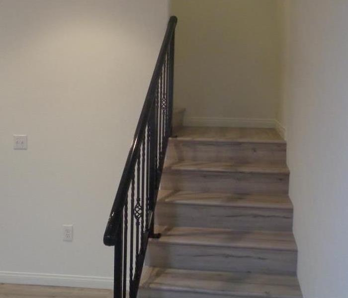 Room with white walls and staircase with black rail