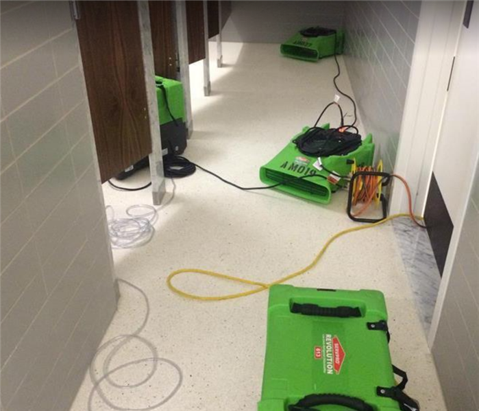 SERVPRO restoration equipment drying bathroom with several stalls