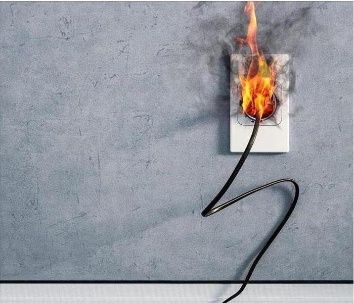 A plug in a wall that is on fire.