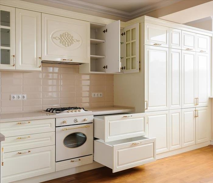 A kitchen with cream colored cabinets and drawers.