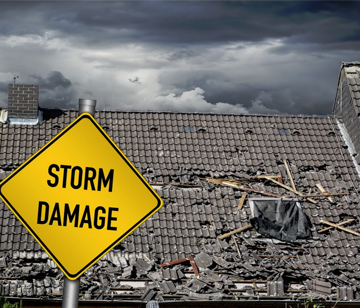yellow diamond storm damage sign in front of dented roof