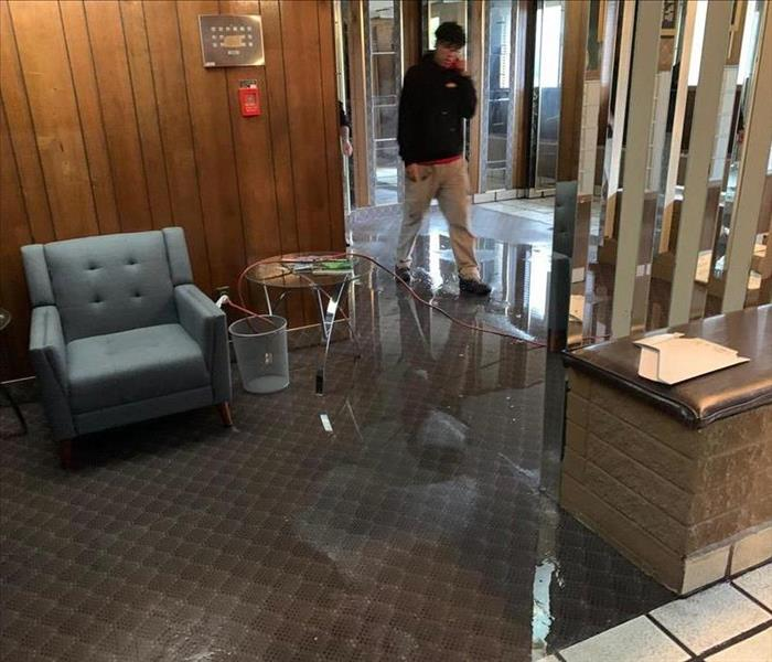 employee standing in office area, water on carpet