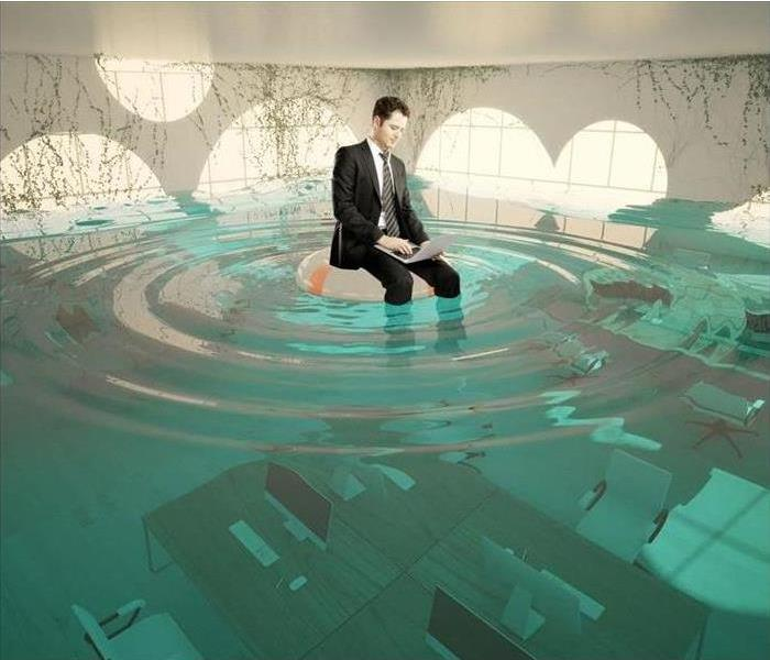 A man sitting on a desk floating in water.